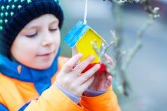 Дом птицы смертной казни через повешение маленького ребенка на дереве для подавать в зиме Стоковое Фото
