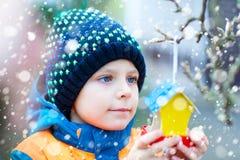 Дом птицы смертной казни через повешение маленького ребенка на дереве для подавать в зиме Стоковые Фото
