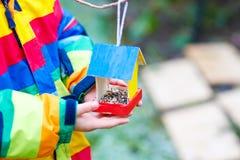 Дом птицы смертной казни через повешение маленького ребенка на дереве для подавать в зиме Стоковая Фотография
