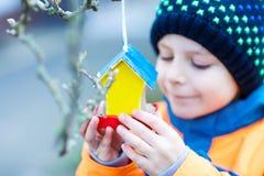 Дом птицы смертной казни через повешение маленького ребенка на дереве для подавать в зиме Стоковая Фотография RF