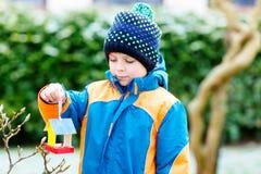 Дом птицы смертной казни через повешение мальчика маленького ребенка на дереве для подавать в зиме Стоковое Изображение RF