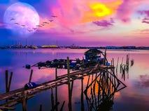 Дом рыбной ловли на ходулях под полнолунием Стоковое фото RF