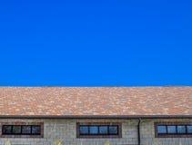 Дом сделан бежевых кирпичей, крыша покрыт с гонт битума Окна металла пластичные на доме стоковая фотография rf