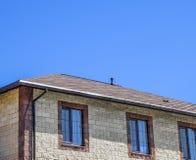 Дом сделан бежевых кирпичей, крыша покрыт с гонт битума Окна металла пластичные на доме стоковые фотографии rf