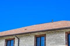 Дом сделан бежевых кирпичей, крыша покрыт с гонт битума Окна металла пластичные на доме стоковое фото