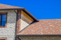 Дом сделан бежевых кирпичей, крыша покрыт с гонт битума Окна металла пластичные на доме стоковая фотография