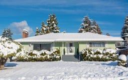 Дом семьи жилой с двором перед входом в снеге на день зимы солнечный стоковое изображение rf