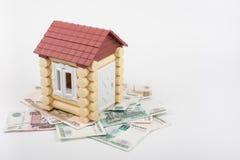 Дом стоит на банкнотах русских рублей, от крыши вставляя из 10 долларов США банкноты Стоковая Фотография RF