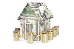 Дом сделанный из денег окруженных загородкой от монеток Стоковые Изображения