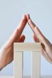 Дом сделанный от блоков игрушки изолированных на белой предпосылке с руками как крыша Стоковое Фото