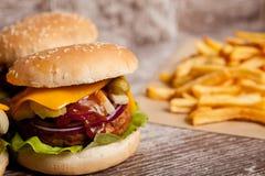 Дом сделал cheeseburgers на деревянной плите Стоковое Изображение
