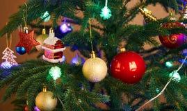 Дом, шарики, звезды и гирлянда освещения на рождественской елке Стоковые Фотографии RF