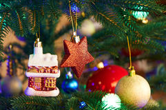 Дом, шарики, звезды и гирлянда освещения на рождественской елке Стоковые Изображения RF