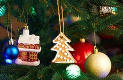 Дом, шарики, печенья и гирлянда освещения на рождественской елке Стоковая Фотография RF