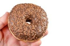 Донут с шоколадом покрывая сливк в руке стоковое изображение rf