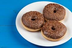 Донут с шоколадом покрывая сливк на голубой предпосылке стоковая фотография