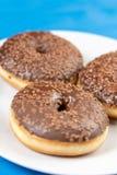 Донут с шоколадом покрывая сливк на голубой предпосылке стоковое фото rf