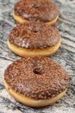 Донут с шоколадом покрывая сливк на сером мраморе стоковые изображения rf