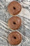Донут с шоколадом покрывая сливк на сером мраморе стоковое изображение rf