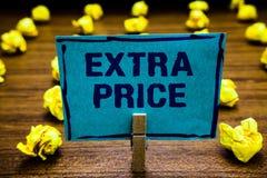 Дополнительная цена текста сочинительства слова Концепция дела для определения дополнительной цены за обычной большой зажимкой дл стоковое фото