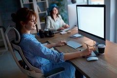 Дополнительное время творческой команды работая на офисе - worki дизайнеров женщин стоковые фото
