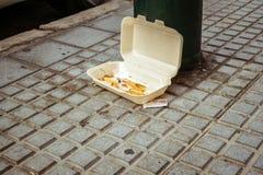 Дополнительные пищевые отходы и утили с и остаток сигареты в пластиковой брошенной коробке стоковая фотография