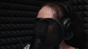 Дополнительный конец вверх молодой привлекательной женщины в наушниках поя к профессиональному микрофону сток-видео