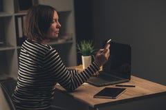 Дополнительное время бизнес-леди работая в офисе Стоковое фото RF