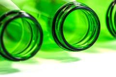 Дополнительный крупный план зеленых бутылок положенных вниз на белую предпосылку Стоковые Изображения RF