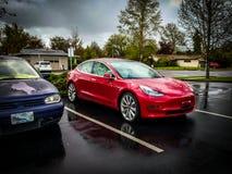 Дорогая спортивная машина припаркованная рядом с дешевым автомобилем стоковая фотография rf