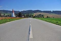 Дорога асфальта и красивая церковь стоковая фотография