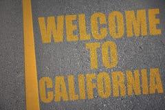 дорога асфальта с гостеприимсвом текста к Калифорнии около желтой линии стоковые фото