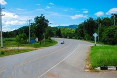 дорога асфальта через зеленое поле и облака на голубом небе в летнем дне в Таиланде Стоковые Изображения RF
