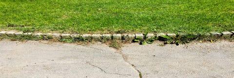 Дорога асфальта через зеленое поле Дорога асфальта пригорода и зеленое травянистое поле ландшафта фокуса поля дня облаков сини не Стоковая Фотография