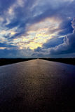 Дорога асфальта и темные облака грома над ей Стоковые Изображения RF