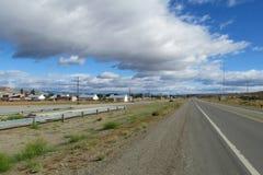 Дорога асфальта идя прямо через деревню стоковые фото