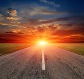 Дорога асфальта к заходу солнца Стоковое Изображение