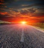 Дорога асфальта на предпосылке захода солнца Стоковая Фотография RF