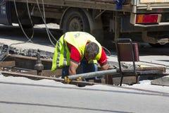 Дорога асфальта стройки работника и железнодорожные линии Стоковые Изображения RF
