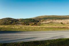 Дорога асфальта через зеленое поле и очищает голубое небо в дне осени Стоковое Фото