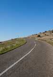 Дорога асфальта через зеленое поле и очищает голубое небо Стоковые Изображения