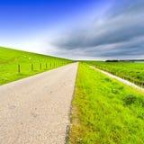 Дорога вдоль защитных запруды и канала стоковое фото