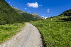 Дорога в высокогорном ландшафте лужка высоких гор на ясном лете, солнечном дне. Стоковое Изображение