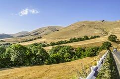 Дорога в горах между пожелтетыми полями в Армении Стоковые Изображения RF