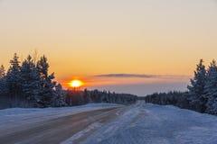 Дорога в зиме на заходе солнца Стоковое Изображение