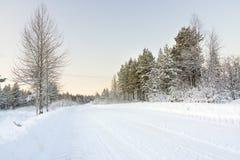 Дорога в зиме на зоре Стоковые Изображения