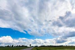 Дорога в открытой местности Зеленое поле, горизонт дерева, грандиозное облако Стоковые Изображения RF