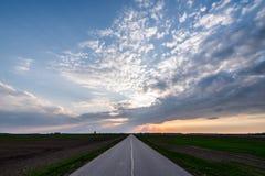 Дорога в полях и пасмурном небе захода солнца весной Литва Стоковая Фотография