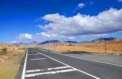 Дорога, голубое небо и вулканы на Фуэртевентуре Стоковая Фотография