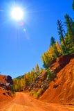 Дорога глины горы богатого красного цвета с осинами и соснами на падении стоковые фотографии rf